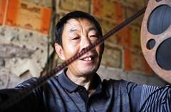 何大银是四川省泸州市江阳区分水岭镇的一名电映放影员,1990年他南下深圳打工,同年因工伤失去了右臂。回乡后,何大银千方百计说服父亲用自已的伤残赔偿金买下电影队的二手电影机,成立仅有一个人的电影队。