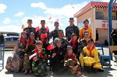 """6月1日是国际儿童节,在海拔4100余米的""""世界高城""""理塘县村戈乡小学里,学生们身着藏族特色节日盛装,踏着《小苹果》欢快的节奏,与理塘兵站官兵一起共庆节日,一派欢歌笑语。"""