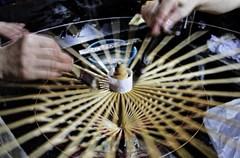 """2015年7月14日,四川省泸州市龙马潭区小市街道的女工们在泸州古典油纸伞厂制作古典油纸伞。近年来,手工制作的古典油纸伞产业在龙马潭区不断发展壮大,该区利用网络平台打造""""互联网+作坊+女工""""模式,以""""订单""""销售方式,每年将富有泸州当地文化元素的50万把以上的舞蹈伞、风景伞、装修伞、道具伞等多类古典油纸伞成品不断销往美国、法国、韩国等10多个国家,并带动众多留守妇女家门口就业。"""