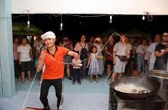 """当日,2018内江第十四届甜城美食文化节在四川内江国际会展中心开幕,汇聚了来自国内外的100余种特色美食。在黄龙溪一根面展位上,拉面小哥表演起花式拉面绝活,表情丰富、动作妖娆,吸引了众多内江市民驻足欣赏。据悉,一根面又叫""""长寿面"""",是成都黄龙溪古镇的传统名小吃,手工制作,一根面拉开,正好装上满满一碗。"""